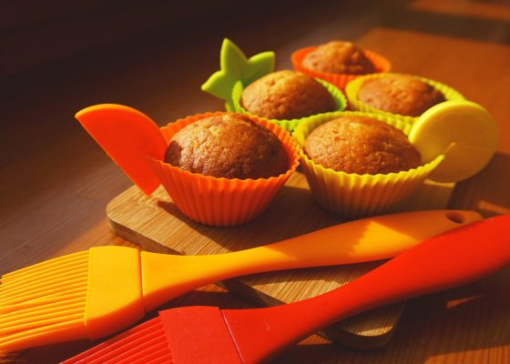 Simple mini muffins in colorful silicone bakeware. Silicone cup baking cupcakes and silicone brushes. Kitchen and cooking concept on wooden background